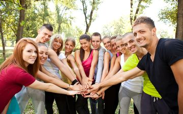group of young people with their hands together outdoor